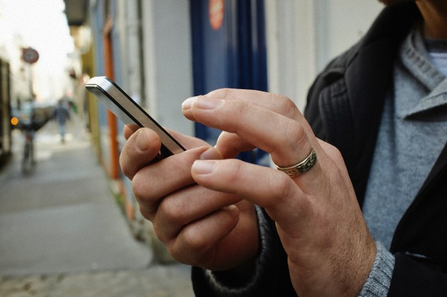 Mid adult man on sidewalk using touchscreen on smartphone